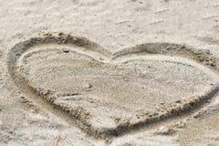 Coeur dessiné dans le sable Seashell de feston sur le rose Vue supérieure Image libre de droits