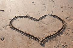 Coeur dessiné dans le sable sur la plage Photos libres de droits