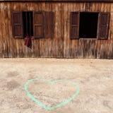 Coeur dessiné par la craie sur l'en bois proche moulu Image stock