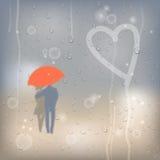 Coeur dessiné sur la fenêtre couverte de baisses de pluie et couples couverts Photographie stock