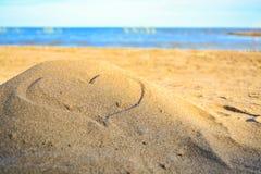 Coeur dessiné sur la plage pendant le coucher du soleil Photographie stock libre de droits
