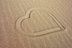 Coeur dessiné sur la plage sablonneuse Photos stock