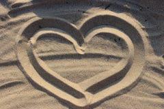 Coeur dessiné sur le sable comme fond d'amour Photo libre de droits