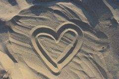 Coeur dessiné sur le sable comme fond d'amour Image libre de droits