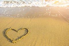 Coeur dessiné sur le sable de la plage d'océan Amour Photo libre de droits