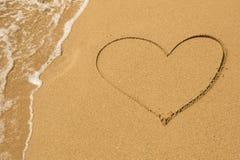 Coeur dessiné sur le sable de plage Image stock
