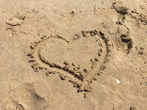 Coeur dessiné sur le sable de plage Amour d'été Photos stock