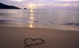 Coeur dessiné sur le sable de plage avec la mousse et la vague de mer Photos libres de droits