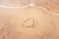 Coeur dessiné sur un sable de plage avec la vague de la mer L'espace libre pour votre texte Concept de vacances d'été Amour roman Images libres de droits