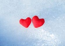 Coeur deux d'un rouge ardent lumineux fait de fil se trouvant sur le froid transpar Photo stock