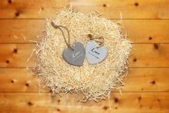 Coeur deux en bois dans un nid d'amour chaud Image libre de droits