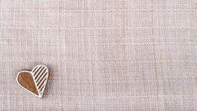 Coeur doux de pain d'épice pour la bonne chance sur le tissu beige Photographie stock