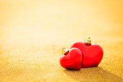 Coeur du bonbon deux sur la lumière chaude de plage de sable Photo stock