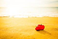 Coeur du bonbon deux sur la plage de sable sous le coucher du soleil et la lumière chaude Photo stock