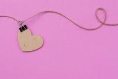 Coeur en bois accrochant sur une corde sur un fond rose Photographie stock