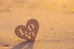 Coeur en bois avec amour d'inscription sur le bord de la mer à l'aube Photo libre de droits