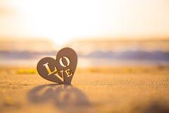 Coeur en bois avec amour d'inscription sur le bord de la mer à l'aube Images libres de droits