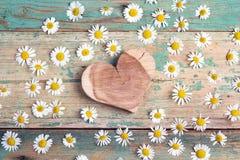 Coeur en bois avec des camomilles sur le fond en bois de vieille turquoise Image libre de droits