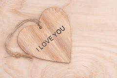 Coeur en bois avec l'amour de mot sur une surface en bois Photo stock
