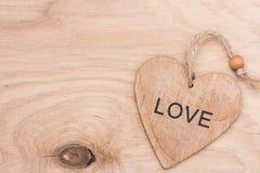 Coeur en bois avec l'amour de mot sur une surface en bois Photo libre de droits