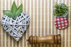 Coeur en bois avec les feuilles et le pot de sauge avec le romarin Image libre de droits