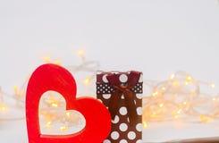 coeur en bois avec un cadeau sur un fond blanc Jour du `s de Valentine Bokeh Photos stock