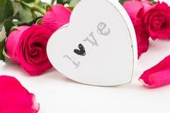 Coeur en bois blanc avec amour de mot là-dessus et un bouquet des roses rouges Photo libre de droits