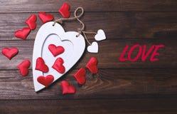 Coeur en bois blanc avec beaucoup de coeurs rouges à côté de l'amour de mot Photographie stock