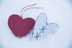 Coeur en bois blanc dans la neige avec le coeur rouge sur le fond de flou Photographie stock libre de droits