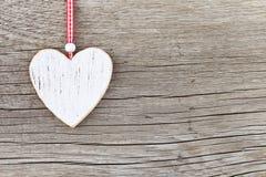Coeur en bois blanc sur un conseil en bois photographie stock