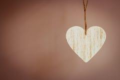 Coeur en bois d'amour accrochant sur le fond de texture Photographie stock