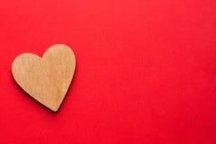 Coeur en bois de Brown sur le fond de papier rouge Photographie stock libre de droits