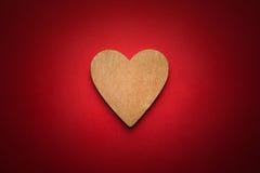 Coeur en bois de Brown sur le fond de papier rouge avec la vignette Photographie stock