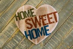 Coeur en bois de message à la maison doux à la maison sur vert clair peint de retour Images stock