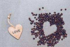Coeur en bois et un coeur des grains de café sur un fond gris Photos libres de droits