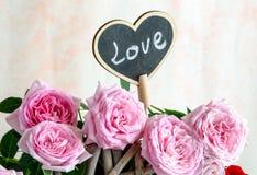 Coeur en bois fait main parmi les roses rouges et roses Photographie stock libre de droits