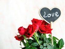 Coeur en bois fait main parmi les roses rouges et roses Photo stock
