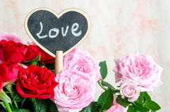 Coeur en bois fait main parmi les roses rouges et roses Images stock