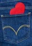 Coeur en bois rouge sortant de la poche de jeans de denim Images libres de droits