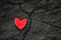 Coeur en bois rouge sur une terre grise sèche criquée Cassé vers le haut du coeur, concept de la vie images stock