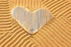 Coeur en bois simple d'amour dans le sable Photographie stock libre de droits