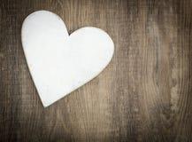 Coeur en bois sur le fond en bois brun de planche Image libre de droits