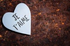 Coeur en bois sur le fond rouillé, mots français pour l'amour Photographie stock libre de droits