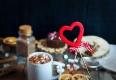 Coeur en bois sur un bâton sur un fond des tasses avec le choco de boissons Image libre de droits