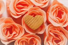Coeur en bois - symbole de l'amour - sur les fleurs roses Image libre de droits