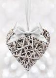 Coeur en bois tressé avec l'arc de ruban d'isolement sur l'argent brouillé Photo libre de droits