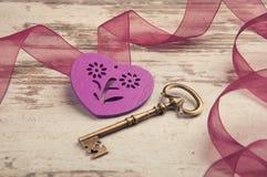 Coeur en bois violet sur le bureau en bois avec la clé Photo libre de droits