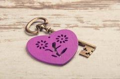 Coeur en bois violet sur le bureau en bois avec la clé Images stock