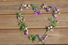 Coeur en fleurs sur le plancher en bois Photographie stock