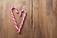 Coeur en l'honneur du jour du ` s de Valentine fait à partir de la canne de sucrerie sur un fond de vieilles planches en bois Images libres de droits